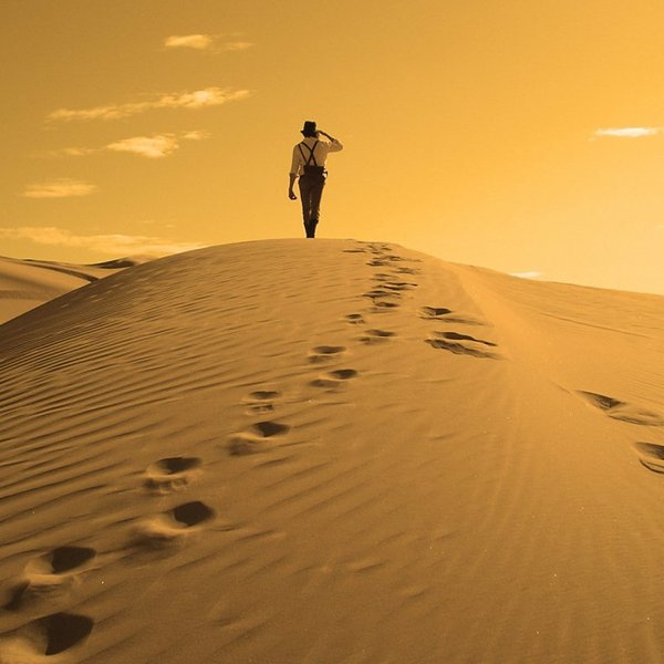 Golden desert sand dune man back footprints walking sky 1024x768